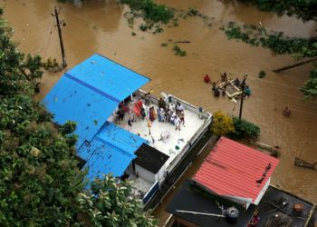 People wait for aid on the roof of their house at a flooded area in the southern state of Kerala, India, August 17, 2018. REUTERS/Sivaram V
