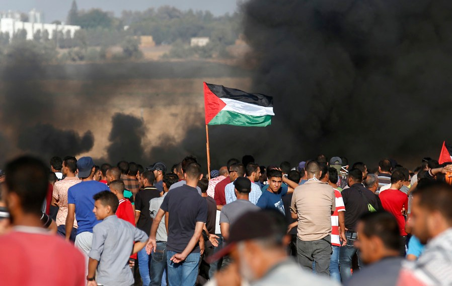 Palestinian protesters wave their national flag as they gather during a demonstration at the Israel-Gaza border, in Khan Yunis in the southern Gaza Strip on August 10, 2018. (photo credit: SAID KHATIB / AFP)