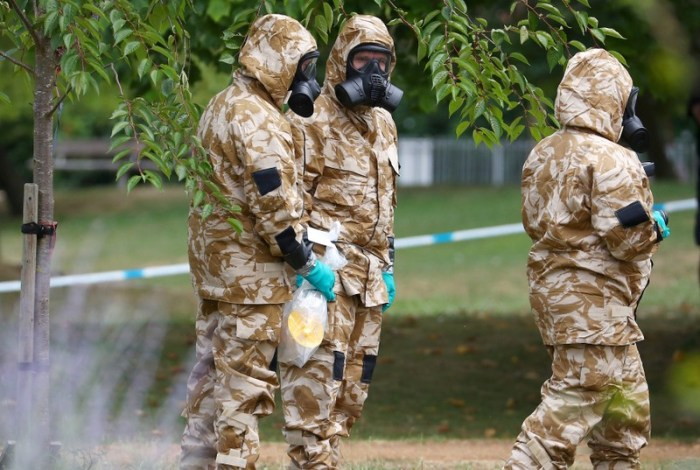 FILE PHOTO: People in military hazardous material protective suits collect an item in Queen Elizabeth Gardens in Salisbury, Britain, July 19, 2018. REUTERS/Hannah McKay/File Photo