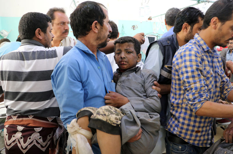 FILE PHOTO: A Yemeni man holds a boy who was injured by an airstrike in Saada, Yemen August 9, 2018./REUTERS/Naif Rahma