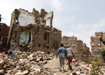 People walk past a house destroyed by an air strike in the old quarter of Sanaa, Yemen Aug 8, 2018. Reuters