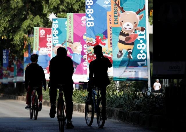 Cyclists ride past banners promoting the upcoming Asian Games, to be held in Jakarta and Palembang, during the weekly car free day in Jakarta, Indonesia July 15, 2018. REUTERS/Darren Whiteside/Files