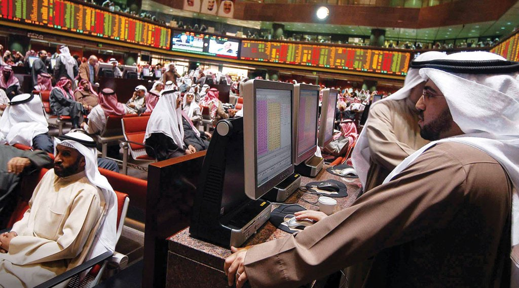 FILE PHOTO: A trader looks at share prices on an electronic display at the Doha Stock Exchange, Qatar January 18, 2016. REUTERS/Naseem Zeitoon/Fiel Photo