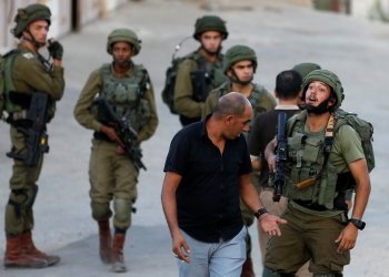 An Israeli soldier argues with a Palestinian man near the scene where a Palestinian, who according to the Israeli military attempted to stab a soldier, was shot dead, in Hebron in the occupied West Bank September 3, 2018. REUTERS/Mussa Qawasma