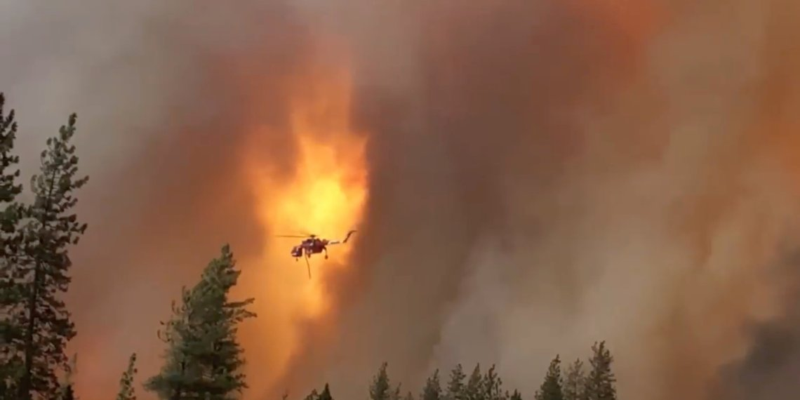 A helicopter drops water on a forest fire in Shasta County in California, U.S., September 5, 2018 in this picture obtained on September 6, 2018 from a social media video. CALIFORNIA HIGHWAY PATROL/via REUTERS