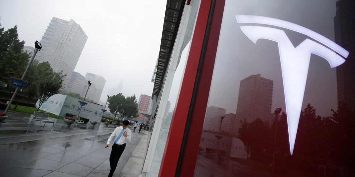 A man walks near a logo of Tesla outside its China headquarters at China Central Mall in Beijing, China July 11, 2018. REUTERS/Jason Lee