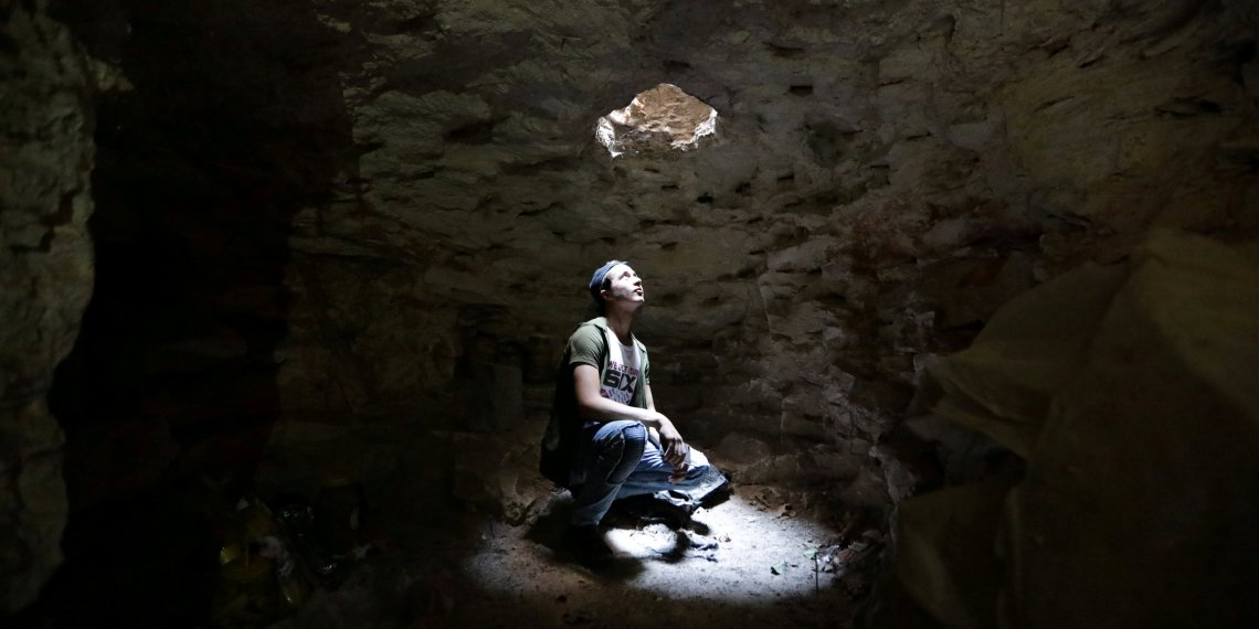 FILE PHOTO: A man looks at an opening from a makeshift shelter in an underground cave in Idlib, Syria September 3, 2018. REUTERS/Khalil Ashawi