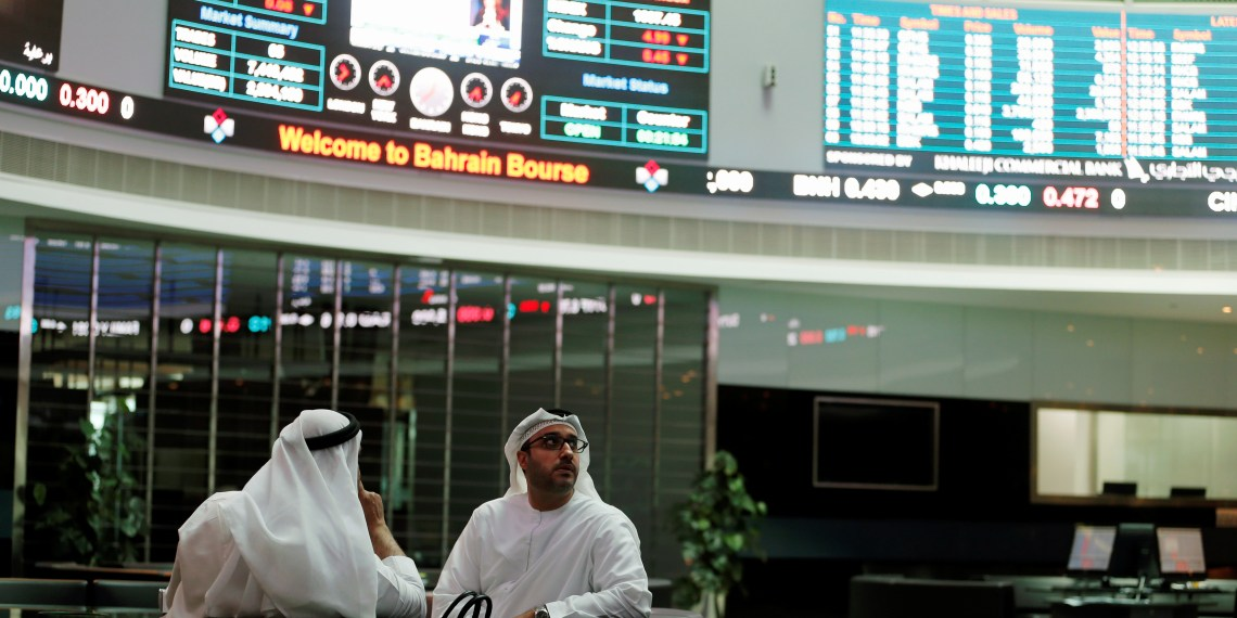 FILE PHOTO: Traders look at the screens at Bahrain Bourse in Manama, Bahrain, February 7, 2018. REUTERS/Hamad I Mohammed/File Photo