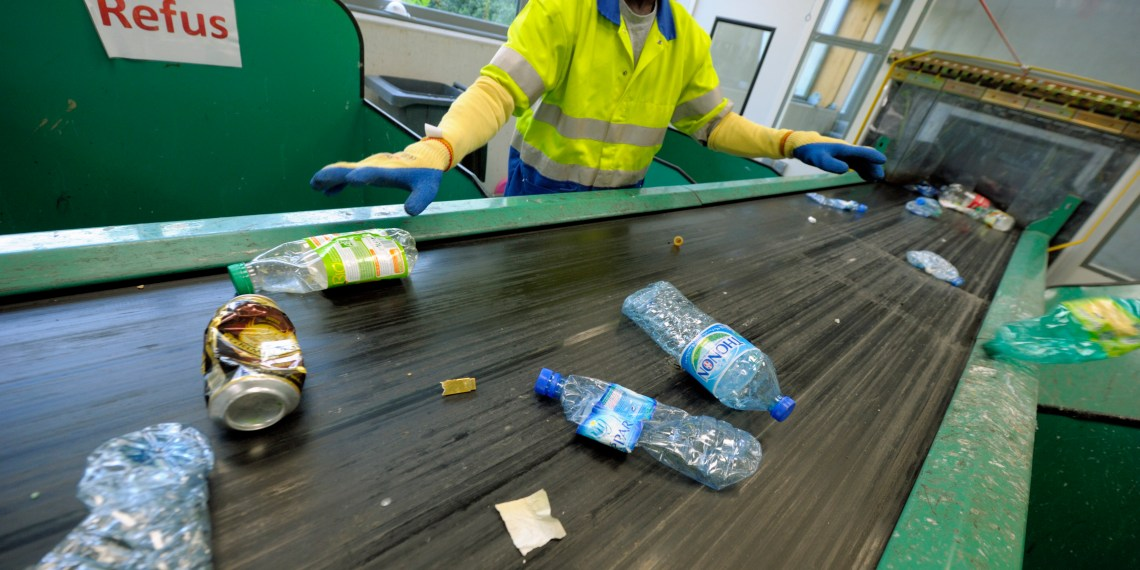 FILE PHOTO: A worker sorts plastic bottles and cans at a recycling centre in Paris May 4, 2011. REUTERS/Philippe Wojazer