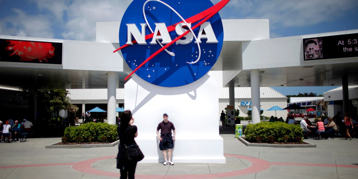 FILE PHOTO: Tourists take pictures of a NASA sign at the Kennedy Space Center visitors complex in Cape Canaveral, Florida April 14, 2010. REUTERS/Carlos Barria