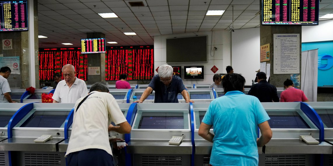 FILE PHOTO: Investors look at computer screens showing stock information at a brokerage house in Shanghai, China September 7, 2018. REUTERS/Aly Song/File Photo