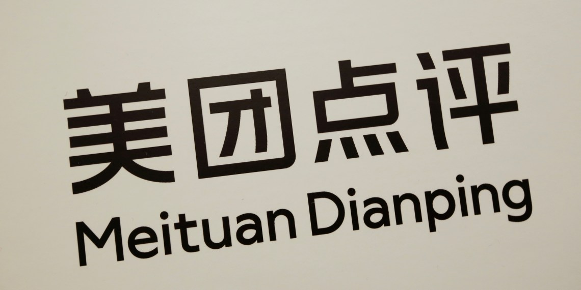 A company logo of China's Meituan Dianping, an online food delivery-to-ticketing services platform, is displayed at a news conference on its IPO in Hong Kong, China September 6, 2018.  REUTERS/Bobby Yip