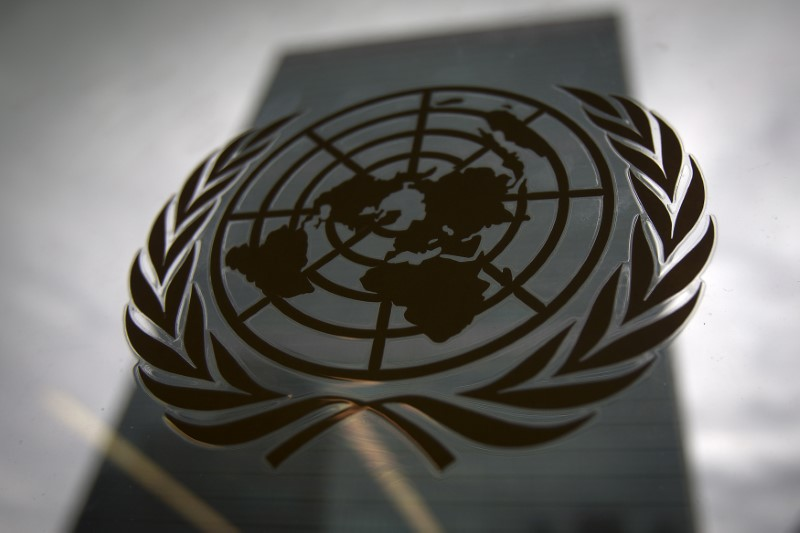 FILE PHOTO - The United Nations headquarters building is pictured though a window with the UN logo in the foreground in the Manhattan borough of New York August 15, 2014. REUTERS/Carlo Allegri