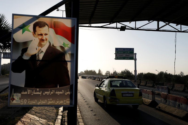 FILE PHOTO: A poster of Syrian President Bashar al-Assad is seen on the main road to the airport in Damascus, Syria April 14, 2018. REUTERS/Omar Sanadiki