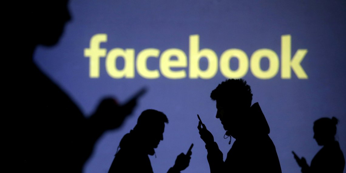FILE PHOTO: Silhouettes of mobile users are seen next to a screen projection of Facebook logo in this picture illustration taken March 28, 2018. REUTERS/Dado Ruvic/File Photo