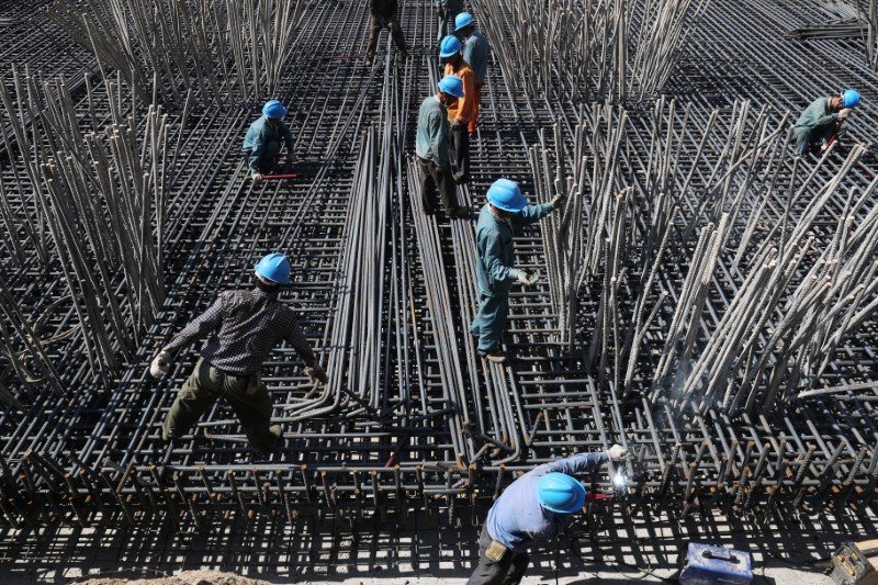 Workers are seen amid steel bars at a construction site of a highway in Zhaotong, Yunnan province, China April 20, 2018. Picture taken April 20, 2018. REUTERS/Stringer