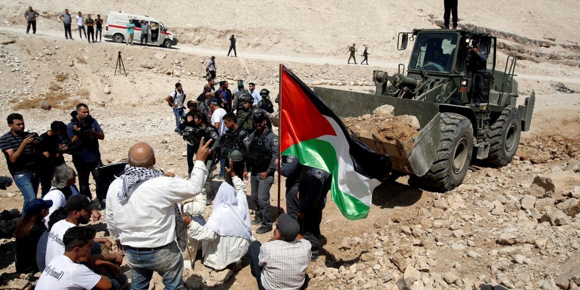 FILE PHOTO: Palestinians gather in front of an Israeli bulldozer as they protest against Israel's plan to demolish the Palestinian Bedouin village of Khan al-Ahmar, in the occupied West Bank September 14, 2018. REUTERS/Mussa Qawasma/File Photo