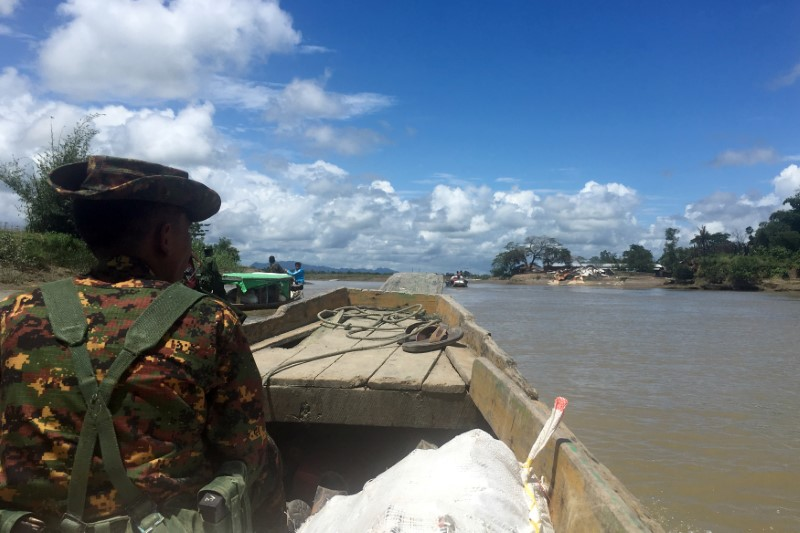 FILE PHOTO: A Myanmar soldier patrols in a boat at the Mayu river near Buthidaung in the north of Rakhine state, Myanmar September 13, 2017. REUTERS/Stringer