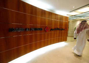 FILE PHOTO: A man walks past a sign at the Majid Al Futtaim headquarters in Dubai during the Reuters Consumer and Retail Summit September 11, 2012. REUTERS/Jumana ElHeloueh