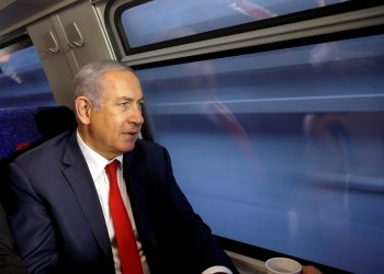 FILE PHOTO: Israeli Prime Minister Benjamin Netanyahu looks out of a train window as he participates in a test-run of the new high-speed train between Jerusalem and Tel Aviv, near Lod, Israel September 20, 2018. REUTERS/Ronen Zvulun/File Photo