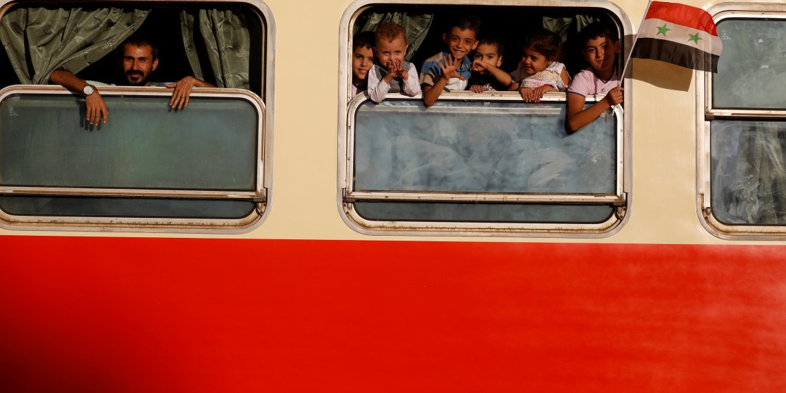 Boys gesture as they look out of a train window at a railway station in Damascus, Syria September 7, 2018. Picture taken September 7, 2018. REUTERS/ Omar Sanadiki
