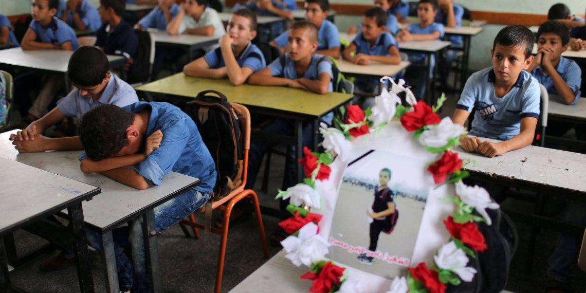 A picture of 12-year-old Palestinian boy Nassir al-Mosabeh, who was killed during a protest at the Israel-Gaza border fence, is seen on his table as his classmates react at a school, in Khan Younis in the southern Gaza Strip September 30, 2018. REUTERS/Ibraheem Abu Mustafa