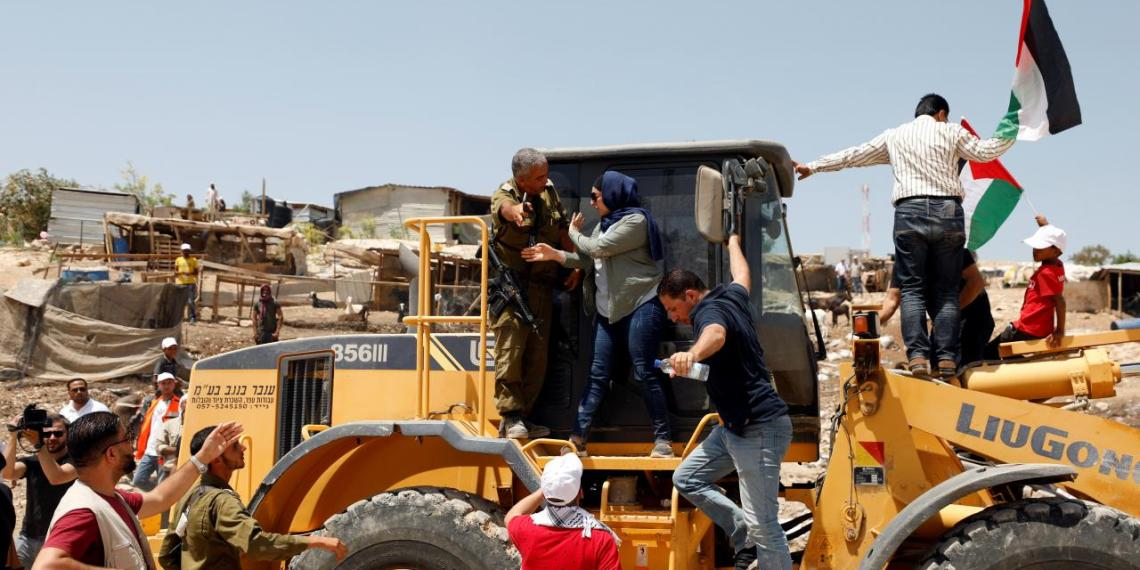 FILE PHOTO: A Palestinian woman argues with an Israeli soldier as she rides on an Israeli bulldozer in the Palestinian Bedouin village of al-Khan al-Ahmar near Jericho in the occupied West Bank July 4, 2018. REUTERS/Mohamad Torokman
