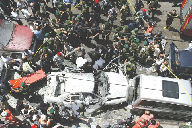 Police and rescue workers gather around the car of Lebanese journalist Samir Kassir, after the car bomb explosion in Beirut that killed him in 2005. (AFP)