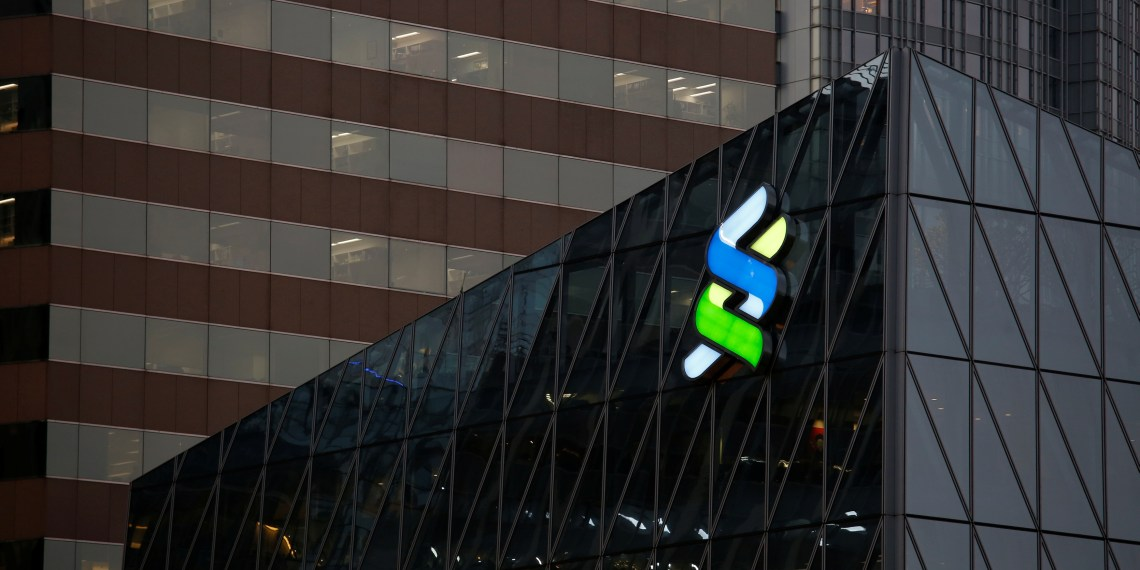 FILE PHOTO: A logo of Standard Chartered is displayed at the financial Central district in Hong Kong, China November 23, 2017. REUTERS/Bobby Yip