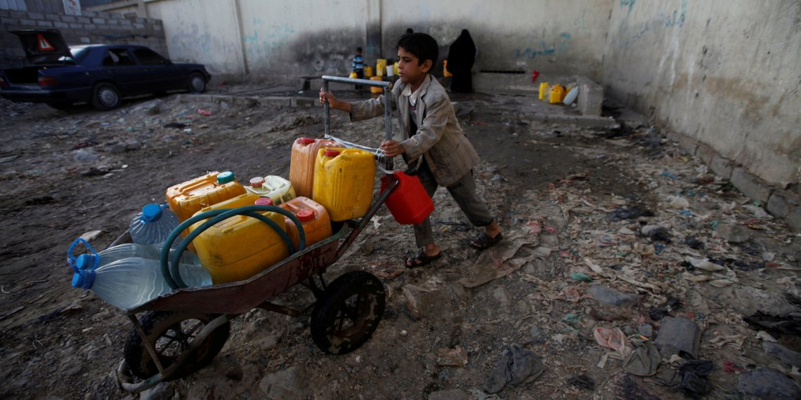 FILE PHOTO: A boy pushes a wheelbarrow filled with water containers after collecting drinking water from a charity tap, amid a cholera outbreak, in Sanaa, Yemen October 13, 2017. REUTERS/Mohamed al-Sayaghi/File Photo