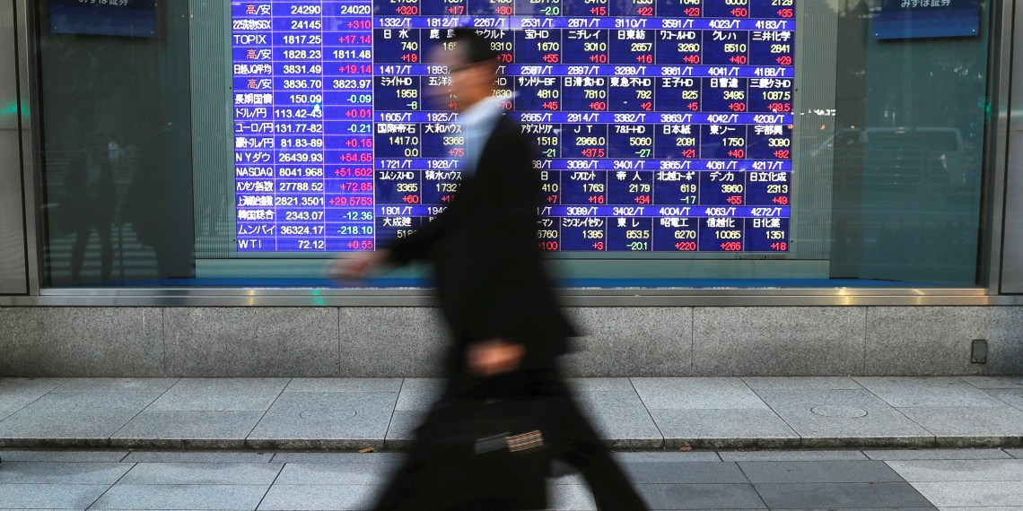 Passersby walk past in front of an electronic stock quotation board outside a brokerage in Tokyo, Japan, September 28, 2018. REUTERS/Toru Hanai/File Photo