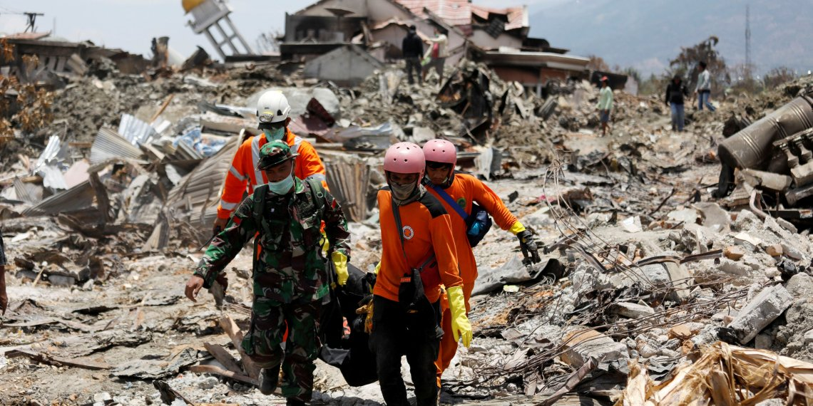 Rescue workers and a soldier remove a victim of last week's earthquake in the Balaroa neighbourhood in Palu, Central Sulawesi, Indonesia October 6, 2018. REUTERS/Darren Whiteside