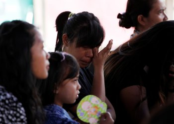 A woman cries while attending an outdoor church service in the earthquake damaged area of Jono Oge village, in Sigi district, south of Palu, Central Sulawesi, Indonesia October 7, 2018. REUTERS/Darren Whiteside