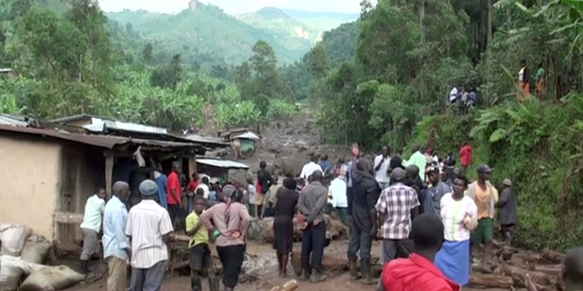 Residents watch flood waters pass through destroyed homes, after a landslide in Bududa, Uganda, in this still image taken from video on October 12, 2018. Reuters TV/via REUTERS