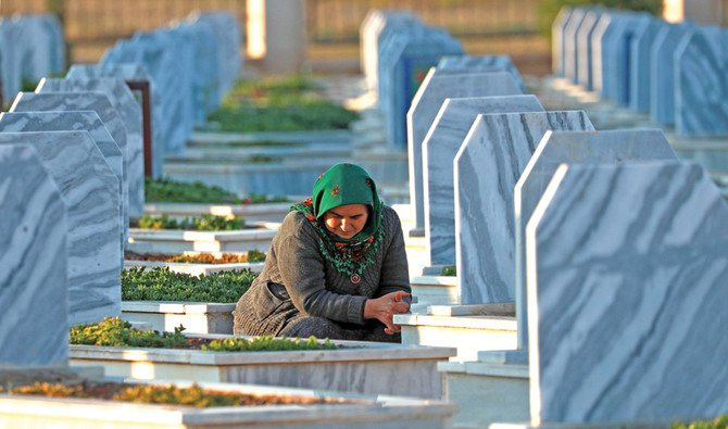 A woman visits the grave of an SDF fighter, killed in a Daesh attack near Deir Ezzor, Syria, on Wednesday. (AFP)