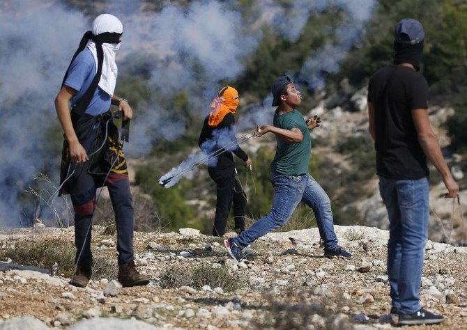 A Palestinian protester throws a tear gas canister towards Israeli soldiers who fired it during a demonstration against Israeli land seizures for Jewish settlements, in the village of Ras Karkar, near Ramallah in the occupied West Bank on November 9, 2018. (AFP)