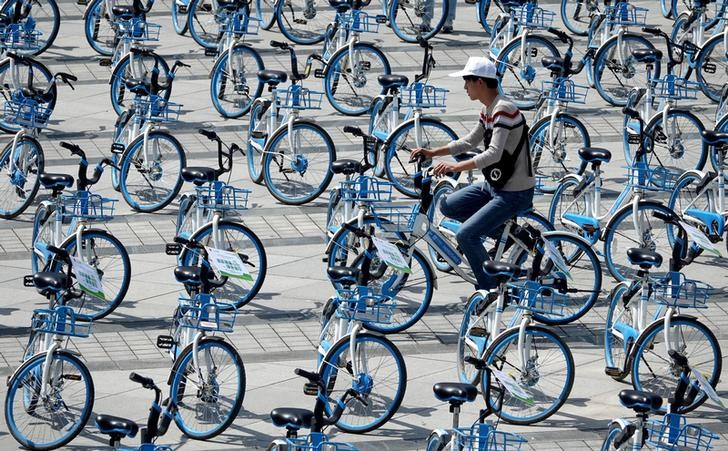 A man rides a bicycle of bike-sharing firm Hellobike amid Hellobike bicycles placed on a plaza a day ahead of the World Car Free Day, in Zhengzhou, Henan province, China September 21, 2018. Picture taken September 21, 2018. REUTERS/Stringer  ATTENTION EDITORS - THIS IMAGE WAS PROVIDED BY A THIRD PARTY. CHINA OUT.