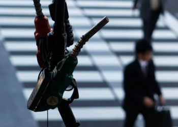 FILE PHOTO: Pedestrians walk near a gas station in Tokyo March 15, 2012. Brent crude inched above $125 on Thursday, after falling more than a dollar the previous session, as traders balanced a firm dollar and bulging U.S. crude stocks with lingering concerns about tensions between Iran and the West.    REUTERS/Toru Hanai