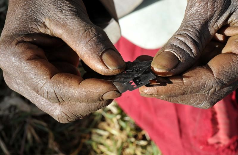 A traditional cutter in Uganda holds razor blades before carrying out female genital mutilation on girls from the Sebei tribe in Bukwa district, northeast of Kampala, December 15, 2008. REUTERS/James Akena