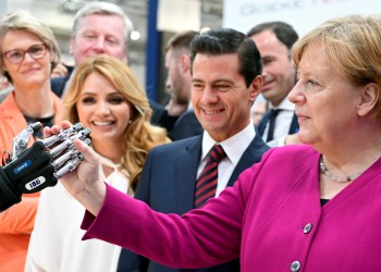 FILE PHOTO: German Chancellor Angela Merkel shakes hands with a humanoid robot as Mexican First Lady Angelica Rivera de Pena and Mexican President Enrique Pena Nieto look on, at the booth of IBG at Hannover Messe, the trade fair in Hanover, Germany, April 23, 2018. REUTERS/Fabian Bimmer/File Photo