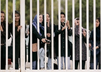 Iranian women watch the practice session of Iran's national soccer team from behind the railings as they banned from entering the stadium at Azadi (freedom) sport complex in Tehran, Iran May 21, 2006. REUTERS/Morteza Nikoubazl
