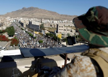 FILE PHOTO: A Houthi militant sits guard on the roof of a building overlooking fellow Houthis rallying to denounce the rapid devaluation of the Yemeni Rial in Sanaa, Yemen October 5, 2018. REUTERS/Khaled Abdullah/File Photo