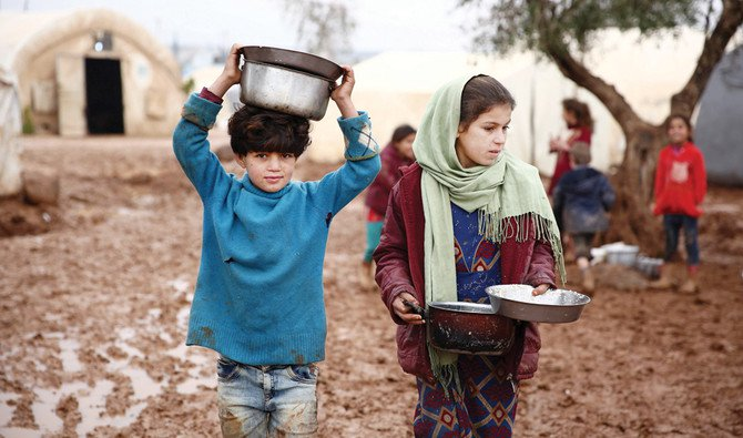 Syrian children carry pots of food at a camp for the displaced near the border with Turkey in the Aleppo province. (File/AFP)