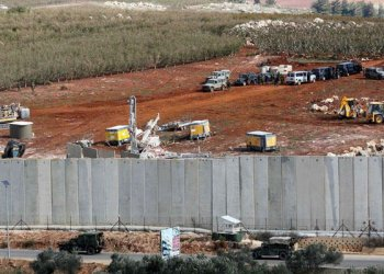A picture taken on December 5, 2018 in the southern Lebanese village of Kfar Kila near the border with Israel shows Israeli machinery (top) operating next to the concrete border wall. (AFP)