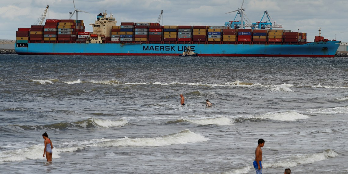 FILE PHOTO: Children play in the sea at New Brighton as the Maersk Line container ship Maersk Sentosa is helped by tugs as it navigates the River Mersey in Liverpool, Britain, July 31, 2018. REUTERS/Phil Noble/File Photo