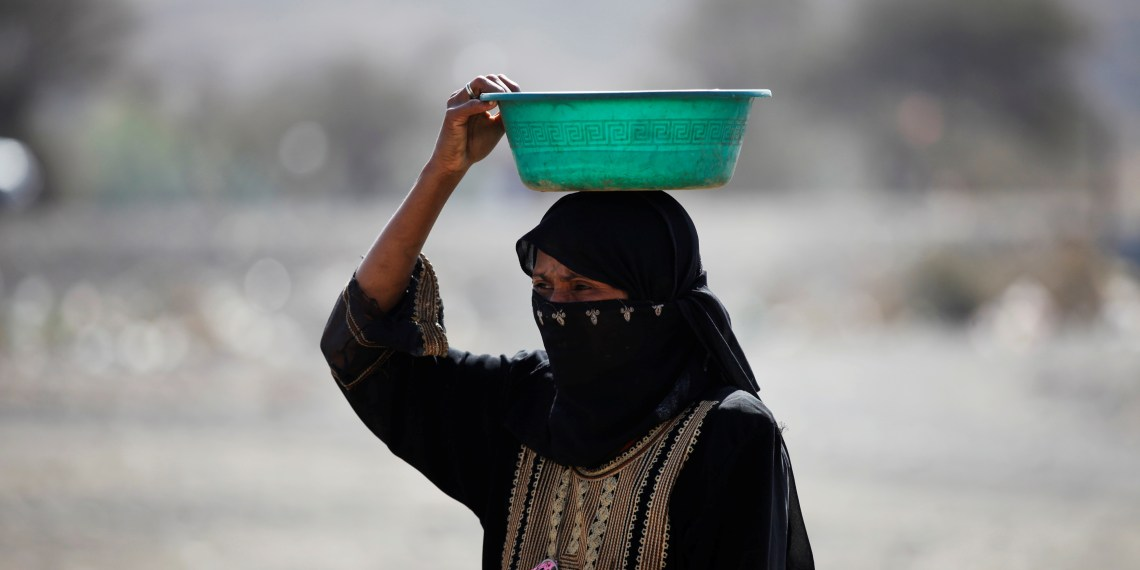 A woman carries a pot at a camp for internally displaced people in Dharawan, near the capital Sanaa, Yemen February 28, 2017. REUTERS/Khaled Abdullah