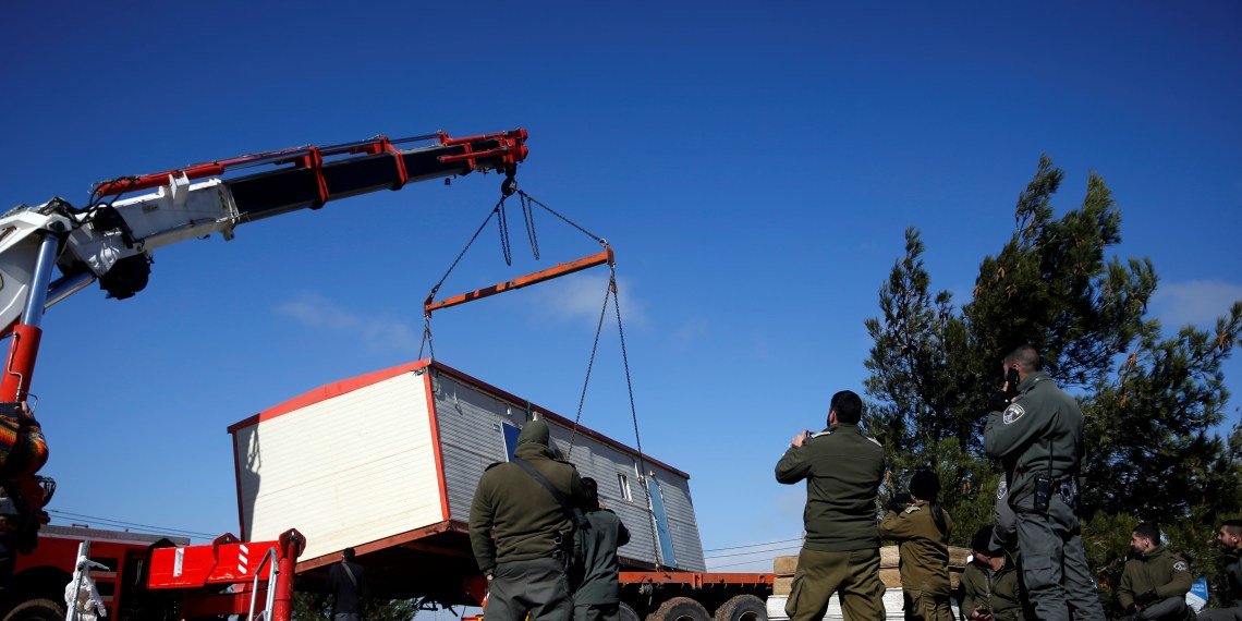 A pre-fabricated home is lowered onto a tow truck as it is removed during an evacuation by Israeli paramilitary police of Jewish settlers from Amona, an illegal outpost in the Israeli-occupied West Bank January 3, 2019. REUTERS/Ronen Zvulun