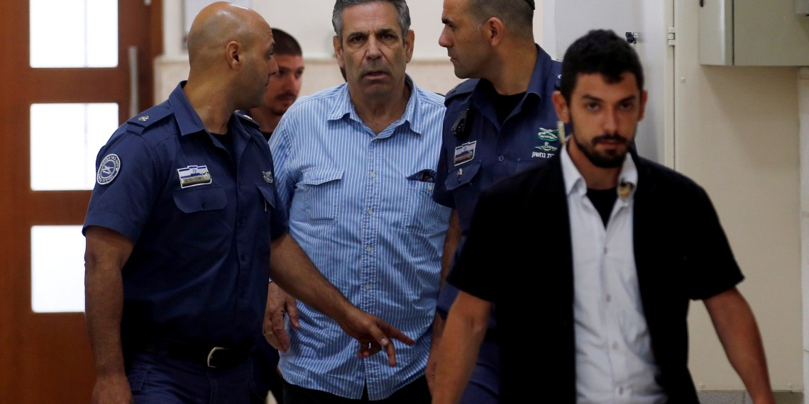 File Photo: Gonen Segev, a former Israeli cabinet minister indicted on suspicion of spying for Iran, is escorted by prison guards as he arrives to court in Jerusalem, July 5, 2018  REUTERS/Ronen Zvulun/ FILE PHOTO