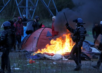 FILE PHOTO: A burning tent is seen, as French riot police push back Iranian Kurdish migrants, during the dismantling of a camp in Calais, France, January 10, 2019. REUTERS/Pascal Rossignol
