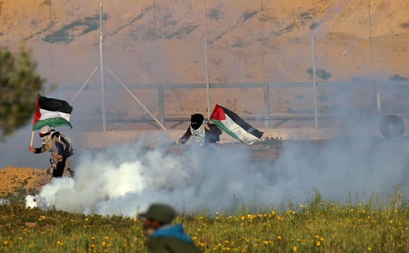 Women holding Palestinian flags run away from tear gas fired by Israeli forces during a protest at the Israel-Gaza border fence, in the southern Gaza Strip February 8, 2019. REUTERS/Ibraheem Abu Mustafa